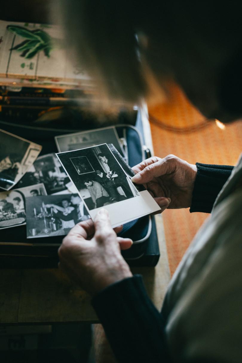 Ruth Wolf-Rehfeldt betrachtet ein Foto, auf dem ihr Mann (mit Gitarre) zu sehen ist.
