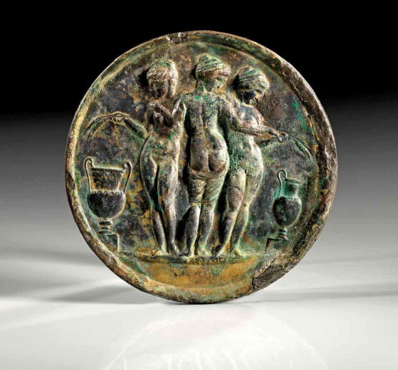 Runder Spiegel, Bronze, Reliefdarstellung der drei Grazien, römisch, 1.–3.Jh., ø12,5cm (Foto: Gerhard Hirsch Nachf., München)