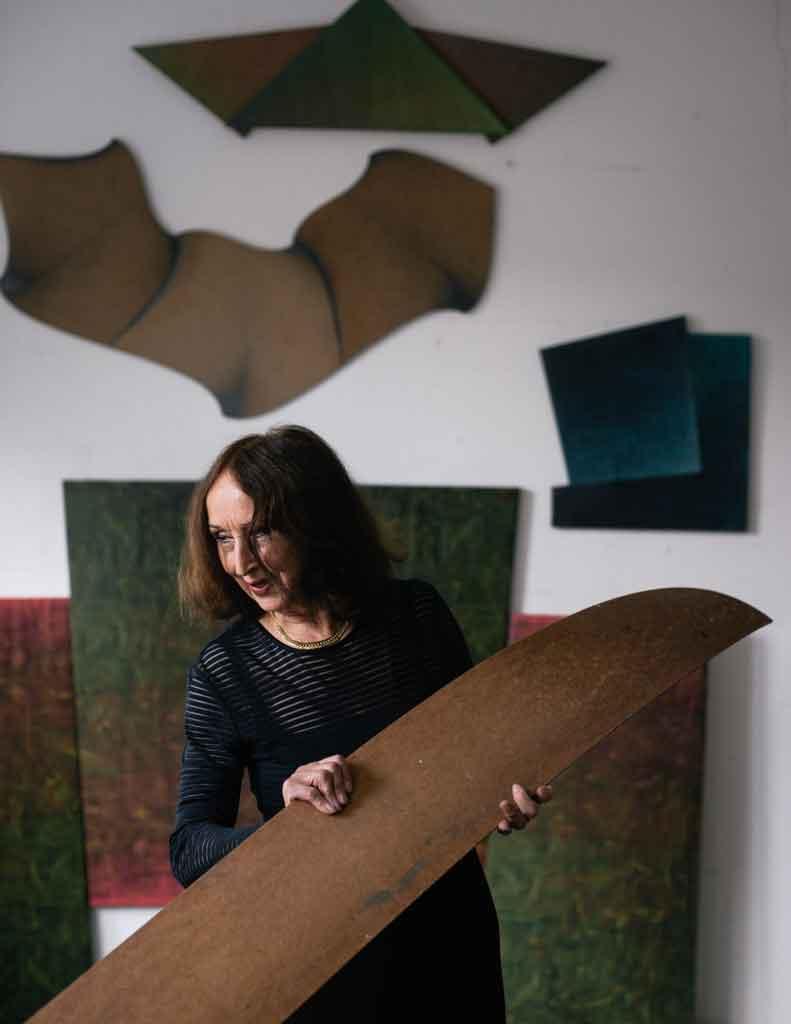 Ingrid Adler im Atelier ihres Mannes mit einem Schablonenholz
