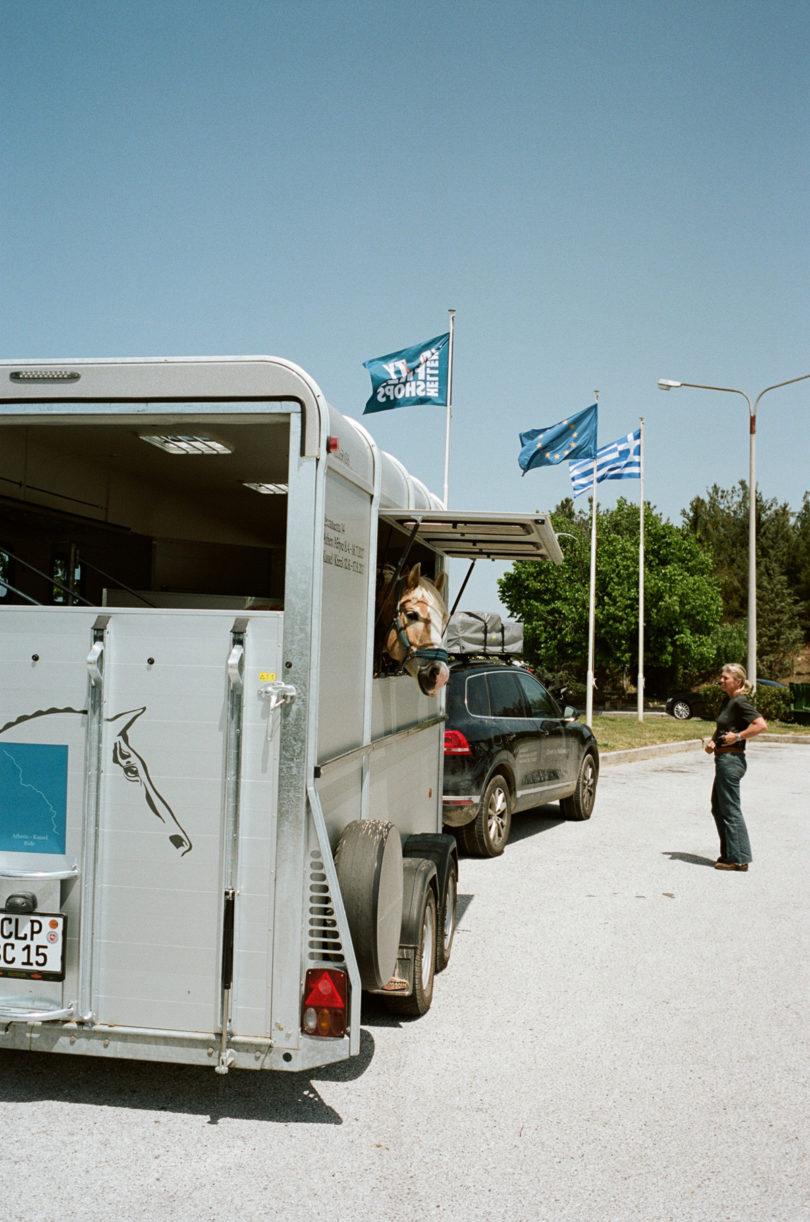 Auf einem Parkplatz im Niemandsland zwischen griechischer und mazedonischer Grenze, Paco lugt neugierig aus dem Anhänger. (Foto: Lukas Gansterer)