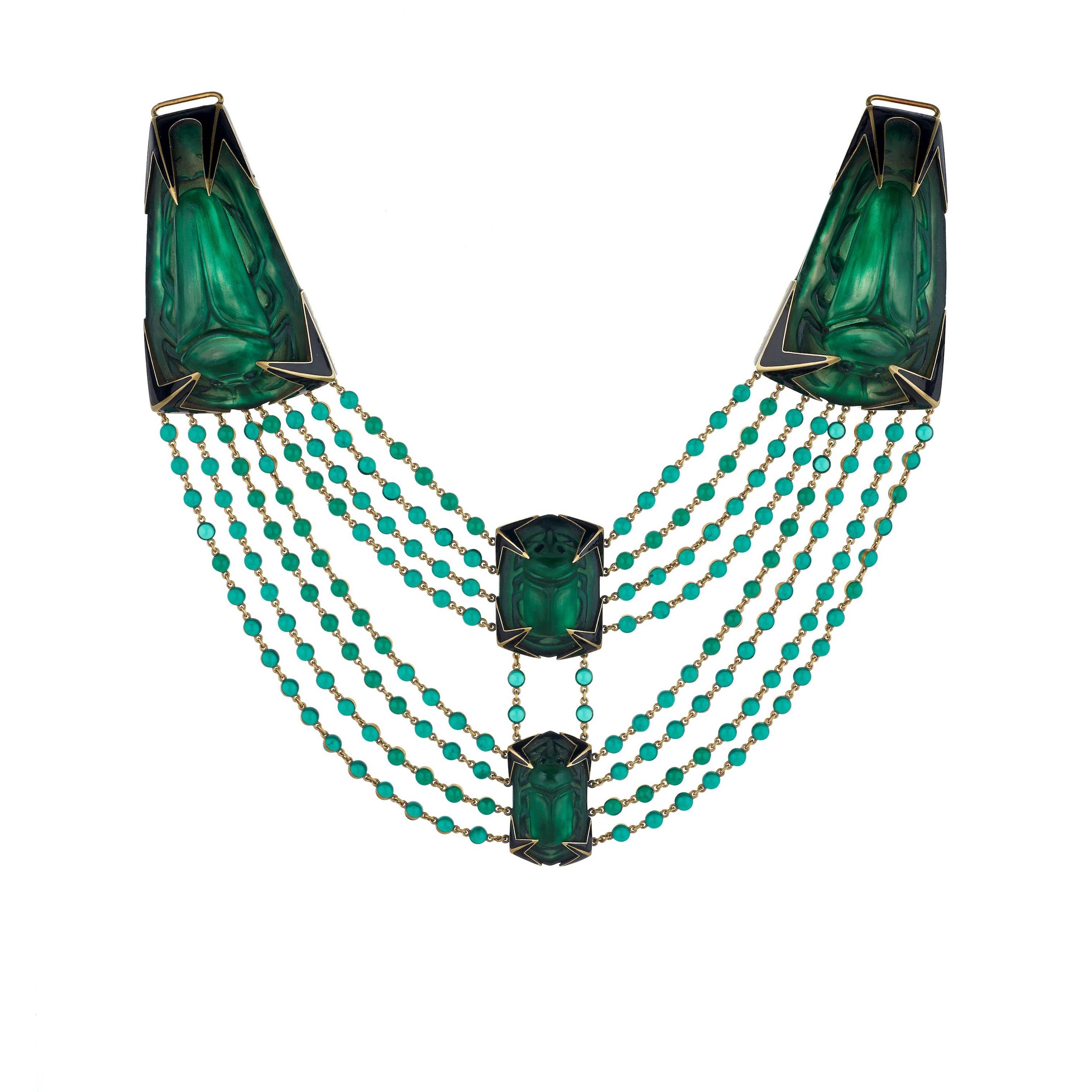 Grünes Leuchten Ab 1890 experimentierte René Lalique mit Glas, um daraus Schmuck zu formen. Als knapp zehn Jahre später sein Collier im ägyptischen Stil entstand, war der legendäre Pariser Gestalter auf der Höhe seiner Kunst: Acht Reihen luzider grüner Perlen werden von vier gläsernen Elementen in Form grüner Skarabäen gehalten. Die goldene Fassung mit ihren schwarz emaillierten Dornen machen das außer-gewöhnliche Stück des Art déco komplett. Angeboten wird es vom Londoner Juwelenhändler Wartski Ltd. für einen sechsstelligen Betrag. Foto: Wartski
